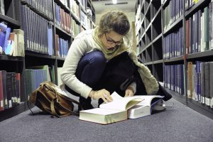 Student with book in SOAS library