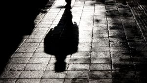 Image of shadow of black person on tiled street