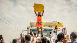 Nigerian woman holding up a sign saying 'STOP KILLING US' and '#endsarsnow'