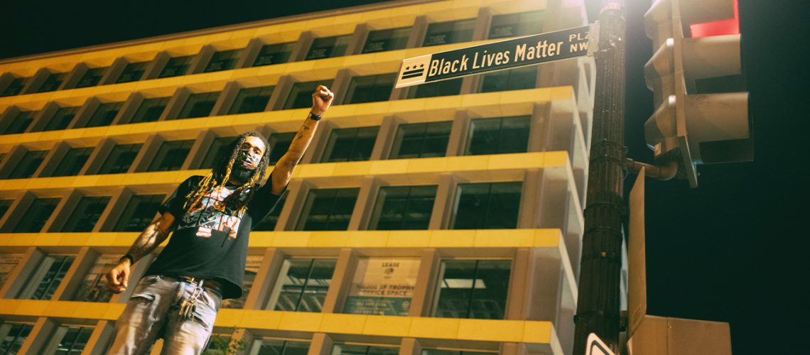Black History Month 2020 - A Black Lives Matter protestor stands beside a road sign which says 'Black Lives Matter'