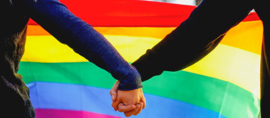 Two girls holding hands and rainbow flag