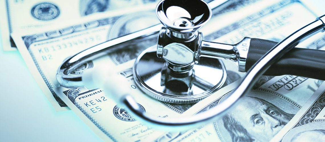 A stethoscope on top of rifled out 100 dollar bills to illustrate health care costs