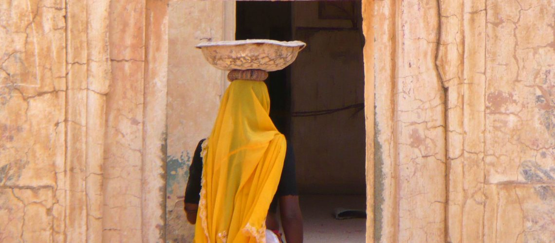 taken at Agra Fort in the Agra District, India. The woman pictured here was part of a group of women working on the reconstruction of the Fort. She is carrying a metal bowl filled with cement on her head.