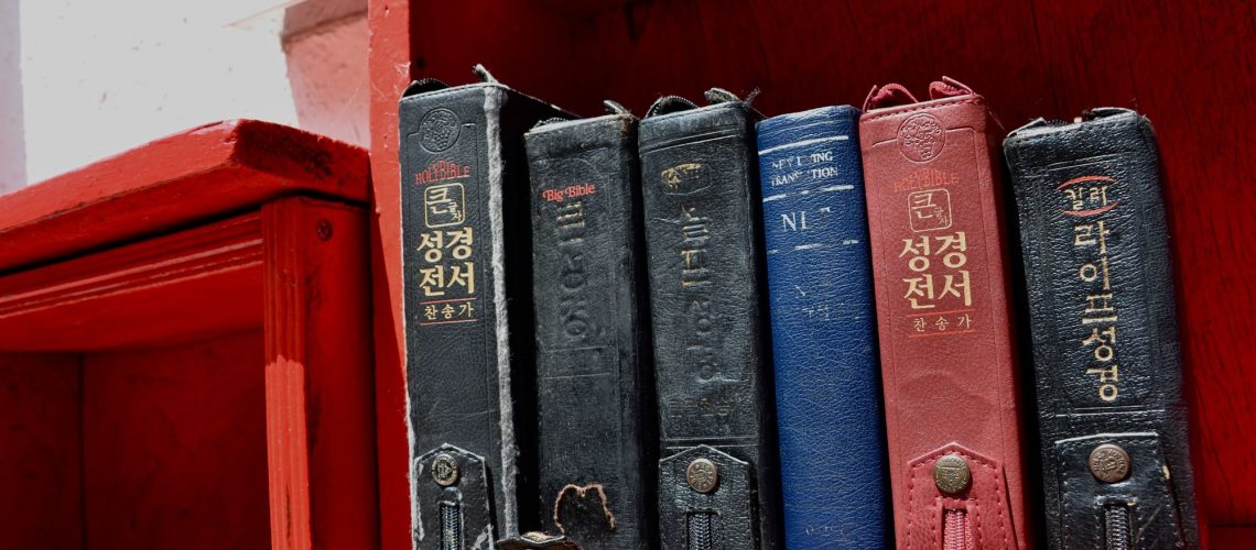 Korean translations of the Holy Bible sit on a shelf with Japanese characters overseen on a wall behind it, a reminiscence of the Japanese colonization in Busan, South Korea.