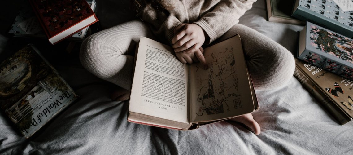 person on bed reading book