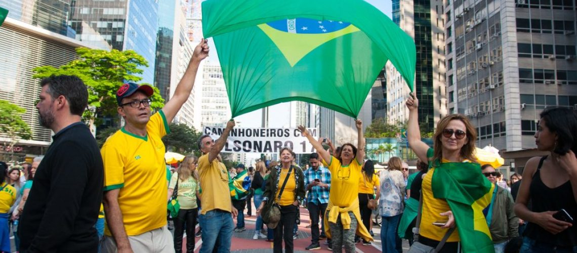 Demonstration for presidential candidate Jair Bolsonaro on Paulista Avenue - quartet holds brazilian flag over air vent sign reads truckers support Bolsonaro