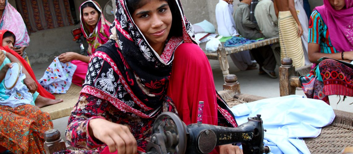 Punjab,,Pakistan,-,February,,2019:,Girl,Smiling,While,Sewing,Traditional